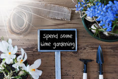 Sunny Spring Flowers, Sign, Text Spend Some Time Gardening. Sign With English Text Spend Some Time Gardening. Sunny Spring Flowers Like Grape Hyacinth And Crocus Stock Photography