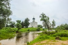 Sunny spring landscape. White church on the river, in the countryside Royalty Free Stock Photos
