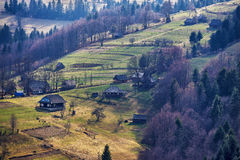 Sunny spring in mountain village. Fields and hills Stock Images