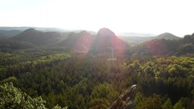 Sunny spring sunrise in a beautiful valley of Saxony Switzerland park. Sandstone rocks. Increased from green pine forest, gentle wind is shaking with leaves stock video footage