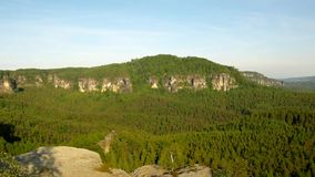 Sunny spring sunrise in a beautiful valley of Saxony Switzerland park. Sandstone rocks. Increased from green pine forest, gentle wind is shaking with leaves stock video