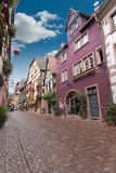 Sunny street in Alsace old town, Riquewihr. Colorful narrow street with beautiful houses and flowers, Riquewihr, Alsace, France Royalty Free Stock Photo