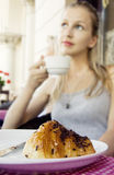 Sunny street coffee cappuccino. Young beautiful blonde is drinking a cappuccino and a croissant at an outdoor cafe and dreams of a pleasant meeting. Cake in Royalty Free Stock Photography