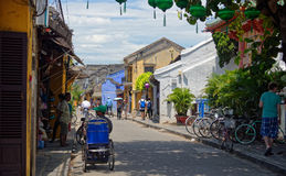 Sunny street in Hoi An, Vietnam. With bicycles, rickshaw,  tourists general merchants shop, tropical plants and tree and overhead lanterns Royalty Free Stock Images