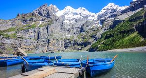 Sunny Summer Activities and recreation, rowing blue boats while enjoying beautiful Swiss alps view on Lake Oeschinen Oeschinensee. Near Kandersteg, Bernese stock photo