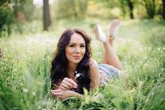 Sunny summer day, a beautiful young woman lying on the grass. Sunny summer day, a beautiful young girl lying on the grass Royalty Free Stock Image