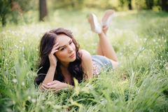 Sunny summer day, a beautiful young woman lying on the grass. Sunny summer day, a beautiful young girl lying on the grass Stock Photography
