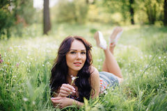 Sunny summer day, a beautiful young woman lying on the grass. Sunny summer day, a beautiful young girl lying on the grass Royalty Free Stock Images
