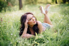 Sunny summer day, a beautiful young woman lying on the grass. Sunny summer day, a beautiful young girl lying on the grass Stock Photo