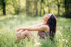 Sunny summer day, a beautiful young woman lying on the grass. Sunny summer day, a beautiful young girl lying on the grass Stock Image
