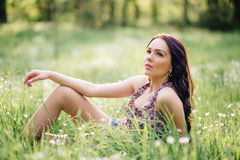 Sunny summer day, a beautiful young woman lying on the grass. Sunny summer day, a beautiful young girl lying on the grass Stock Images