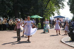 Sunny summer day in the city Park. girls public entertainers dancing with the tourists people under the music of a military brass. Girls public entertainers royalty free stock photo