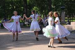 Sunny summer day in the city Park. girls public entertainers dancing with the tourists people under the music of a military brass Stock Images