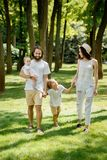 Sunny summer day. Happy young family dressed in the white casual clothes walks in the park. royalty free stock photos