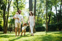 Sunny summer day. Happy young family dressed in the white casual clothes walks in the park. stock images