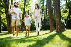 Sunny summer day. Happy young family dressed in the white casual clothes walks in the park. stock photos