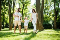 Sunny summer day. Happy young family dressed in the white casual clothes walks in the park. royalty free stock photo