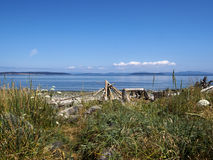 Sunny Summer day on a rocky beach with a Driftwood Tipi Tent like figure in the distance. Beautiful sunny day on Vancouver island by the beach coastline showing Royalty Free Stock Images