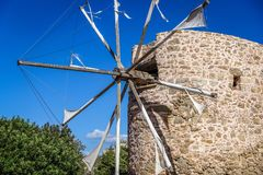 An old windmill on a blue sky background. Sunny summer day, view of very old windmills, beautiful blue sky with some white clouds; An old windmill on a blue sky Royalty Free Stock Photos