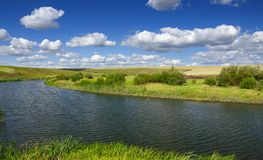 Sunny summer landscape with river,fields,green hills and beautiful clouds in blue sky stock photography