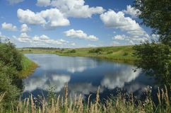 Sunny summer landscape with river,fields,green hills and beautiful clouds in blue sky. stock photography