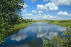 Sunny summer landscape with river,fields,green hills and beautiful clouds in blue sky. stock photos