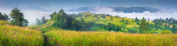Sunny summer panorama of mountain village in morning mist. Royalty Free Stock Photo