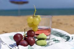 A sunny photo with a glass of wine and grapes against a background of a sand beach and sea. A sunny summer photo with a glass of wine and grapes against a royalty free stock photography