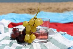 A sunny photo with a glass of wine and grapes against a background of a sand beach and sea. A sunny summer photo with a glass of wine and grapes against a royalty free stock photo