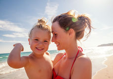 Sunny summertime on the beach. Smiling laughing mother baby on arm Royalty Free Stock Images