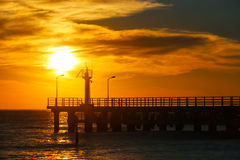 Sunny sunset through pier at the sea Royalty Free Stock Photography