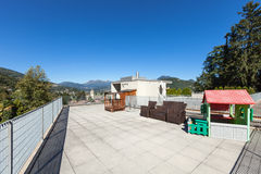 Sunny terrace of house. Sunny terrace of a building, mountains and sky background Stock Photo