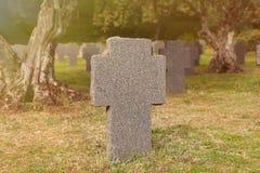 Sunny tomb with stone cross Stock Photos