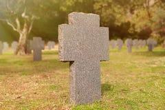 Sunny tomb with stone cross Stock Photo