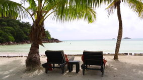 Sunny and tropical beach view with deckchairs, Seychelles. Tropical landscape view at Seychelles stock video footage