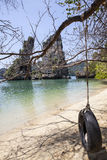 Sunny tropical beach with wheel swing handing on the tree Stock Photography