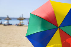 Sunny umbrella. Multicolored umbrella at the beach Royalty Free Stock Image