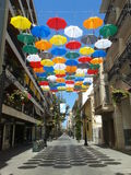 Sunny Umbrellas. Above the streets of Gandia, Spain, hang these brightly coloured umbrellas to depict the start of the sales in the shops. They also offer some Royalty Free Stock Photo