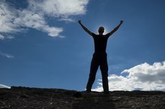 Sunny Victory. A young man reaches his arms up in vitory on a rocky summit.  Sun shines behind the man Royalty Free Stock Images
