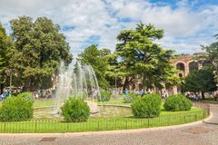 Sunny view of fountain in the park near famous landmark of Verona Arena or Amphitheater. Verona City in Italy. royalty free stock photo