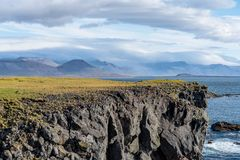 Sunny view of the west coastline of Iceland. With a steep edge of lava cliff down to the ocean below royalty free stock images