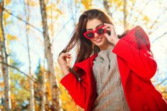 Sunny warm day. A portrait of a beautiful young woman wearing sunglasses in a sunny autumn forest. Lifestyle, autumn fashion, beauty stock image