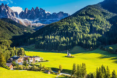 Sunny warm day in Tirol. The symbol of valley Val di Funes - church of Santa Maddalena. Rocky peaks and forested mountains surrounded by green Alpine meadows Stock Photography