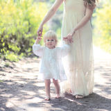 Sunny warm portrait mom and daughter walking in the forest Royalty Free Stock Photos