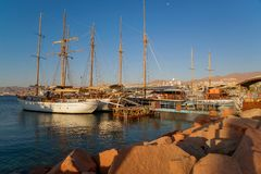 Sunny, warm sunrise on the Red sea shore. In Eilat  wellknown resort with ships, boats and breakwaters stock photos