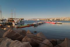 Sunny, warm sunrise on the Red sea shore. In Eilat  wellknown resort with ships, boats and breakwaters royalty free stock photos