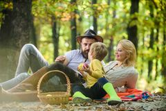 Sunny weather. Healthy food. Family picnic. Mother, cowboy father love their little boy child. Happy son with parents. Relax in autumn forest. Spring mood stock image