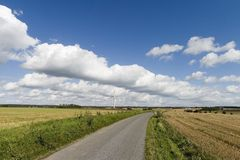 Sunny windmill and a road. Countryside road. Windmill on on a field on a sunny day with nice clouds, Denmark Stock Images