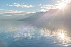Sunlight shining over mountains and Skaha Lake just before sunset in winter Stock Photography
