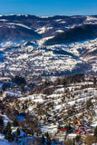 Sunny winter alpine scenery with small Romanian village in the valley of Bucegi Royalty Free Stock Photos